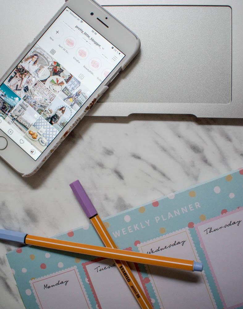 biely iphone, touchpad Airbooku od Apple, časť týždenneho plánovača a dve ledabolo pohodene Stabilo fixky s tenkým hrotom