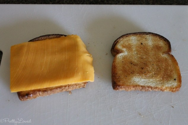 Start assembling your sandwiches. Put two slices of bread down, and add a slice of Cheddar cheese.