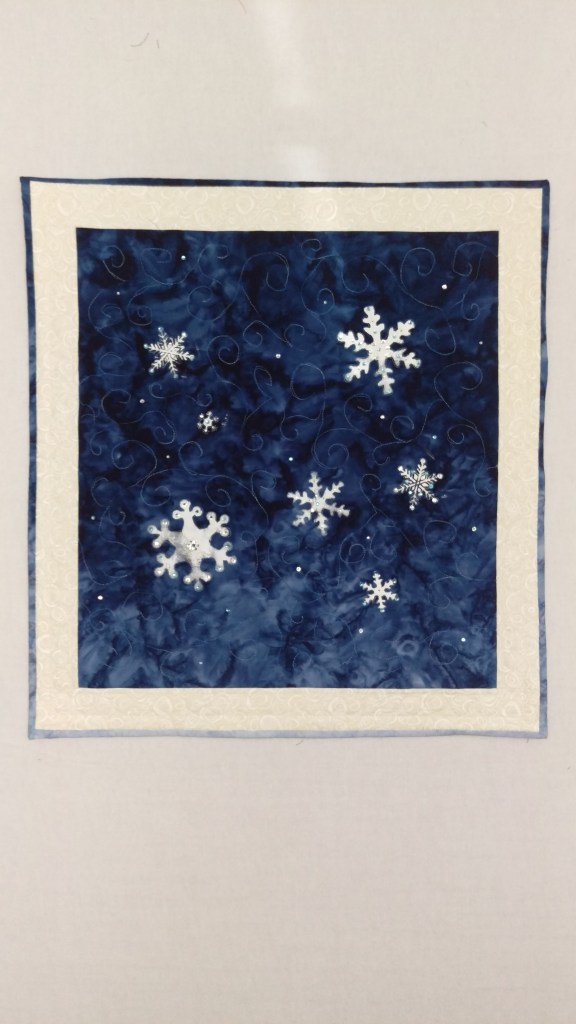 mini quilt featuring stenciled snowflakes and hotfix Swarovski crystals on a blue ombre background