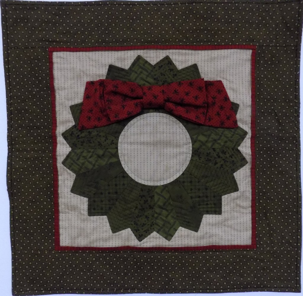 a green dresden wreath with a red fabric bow from Eleanor Burns' book Egg Money Quilts