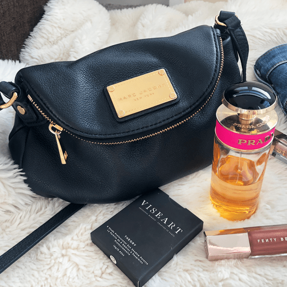 a black leather purse sitting next to a bottle of perfume, eyeshadow palette and lip gloss