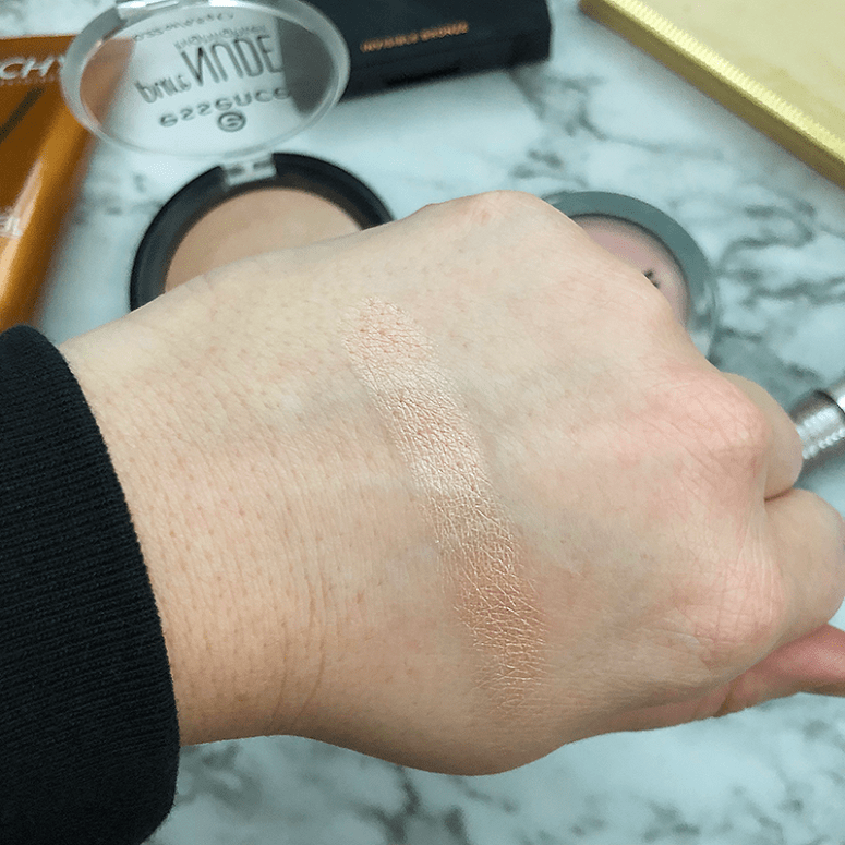 A finger shot of Essence's Pure Nude Highlighter on a white marble background