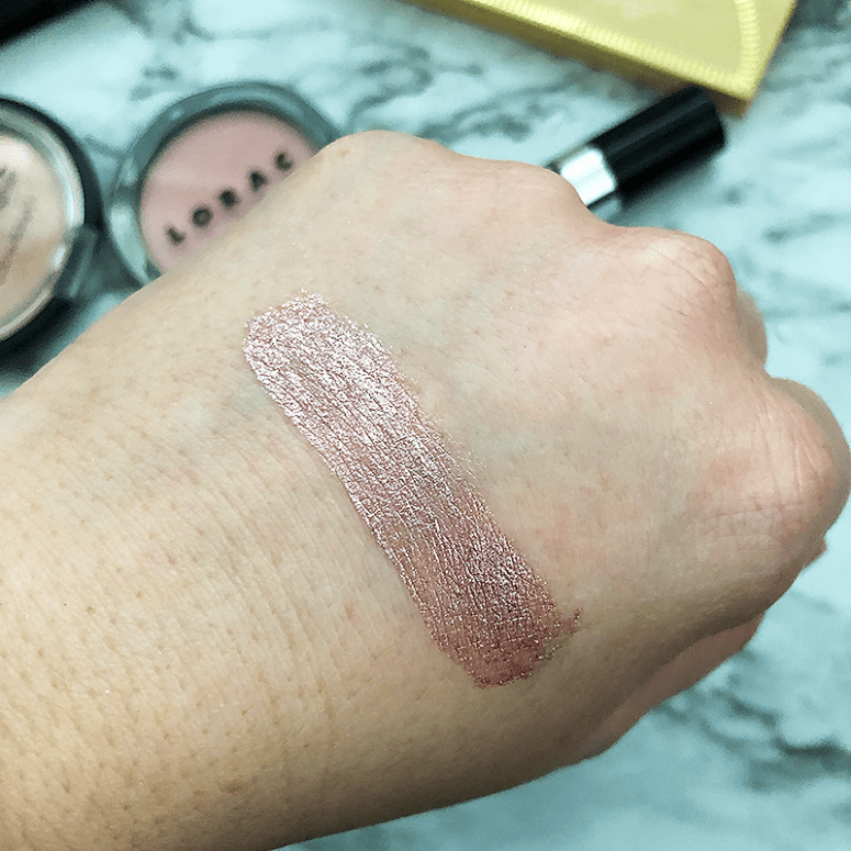 a finger swatch of Essence's Metal Shock Eyeshadow (in the shade Stars & Stories) on a white marble background