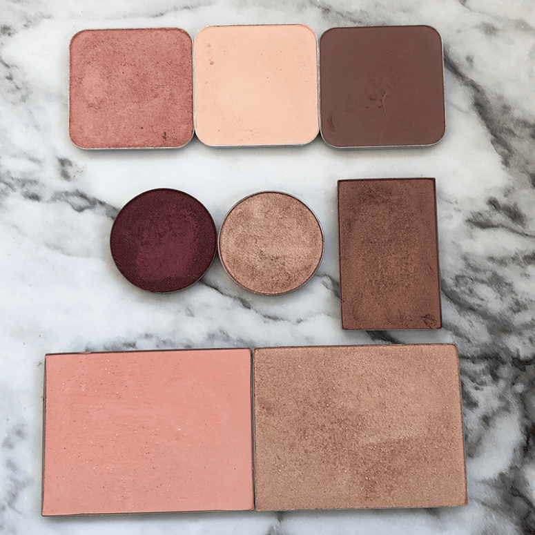 closeups of various pan powder products including Kiko Cosmetics High Pigment Eyeshadow, Anastasia Single Eyeshadows, and Maison Jacynthe eyeshadow, blush and highlighter on a marble background