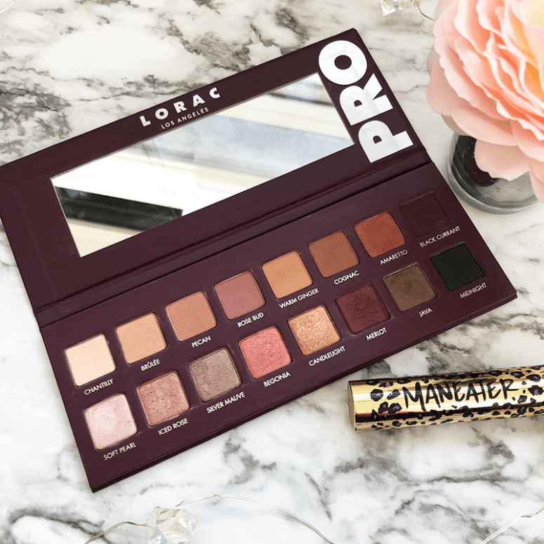 an open Lorac Pro 4 palette sitting on a marble background with a pink rose on the right side and a gold mascara below