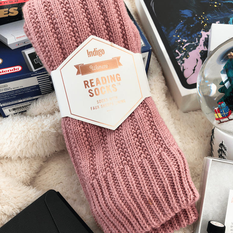 a picture of pink knit reading socks with various items in the background