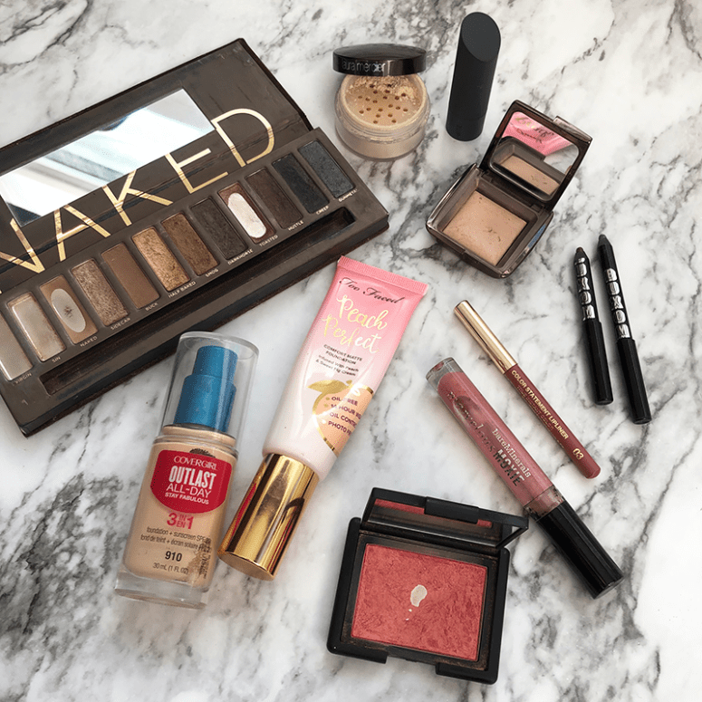 A flat lay photo of various beauty products on a white marble background