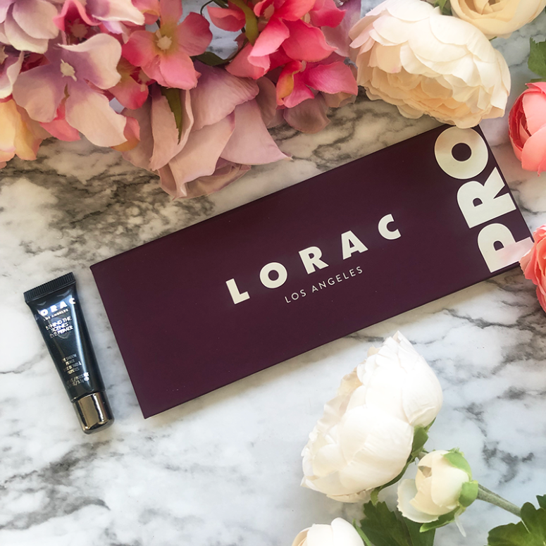 a picture of the Lorac Pro 4 eyeshadow palette and Behind the Scenes Primer on a marble background with flowers around it