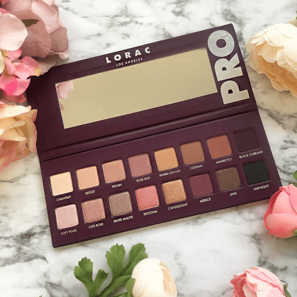A picture of the Lorac Pro 4 palette sitting on a marble background with pink florals surrounding it
