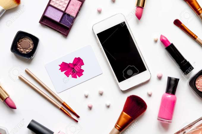 concept online shopping cosmetics on white background top view