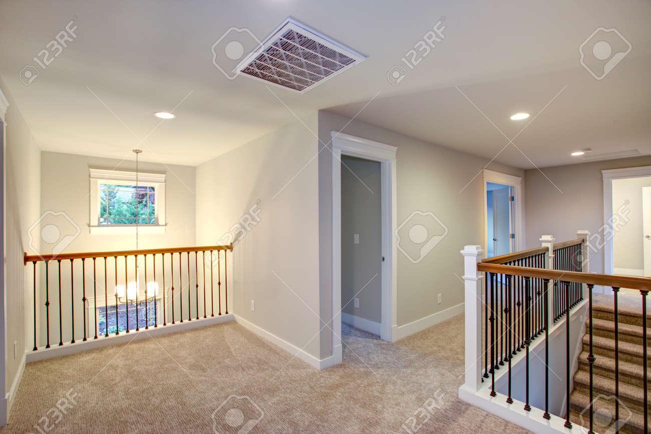 interieur de maison neuve caracterise par un palier au deuxieme etage avec murs de couleur gris clair sol en moquette beige et escalier
