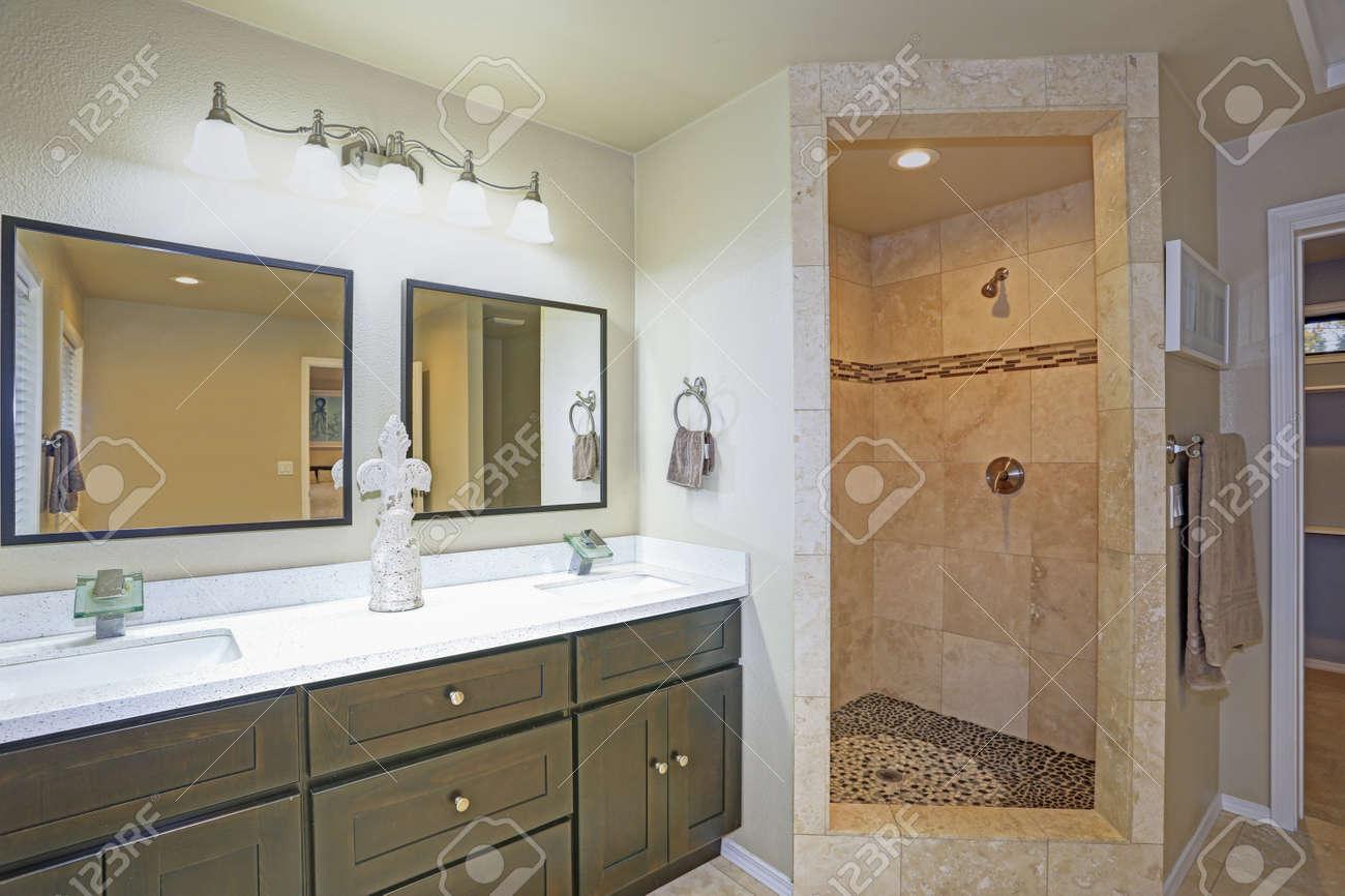 salle de bain principale avec douche de luxe rehaussee de mosaique et double vasque sur carrelage beige