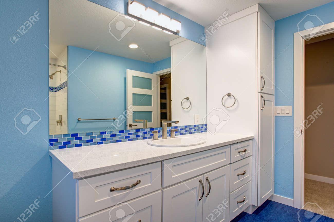 superbe salle de bain aux murs bleus meuble lavabo simple extra large blanc creme avec comptoir en granit et dosseret en mosaique bleue