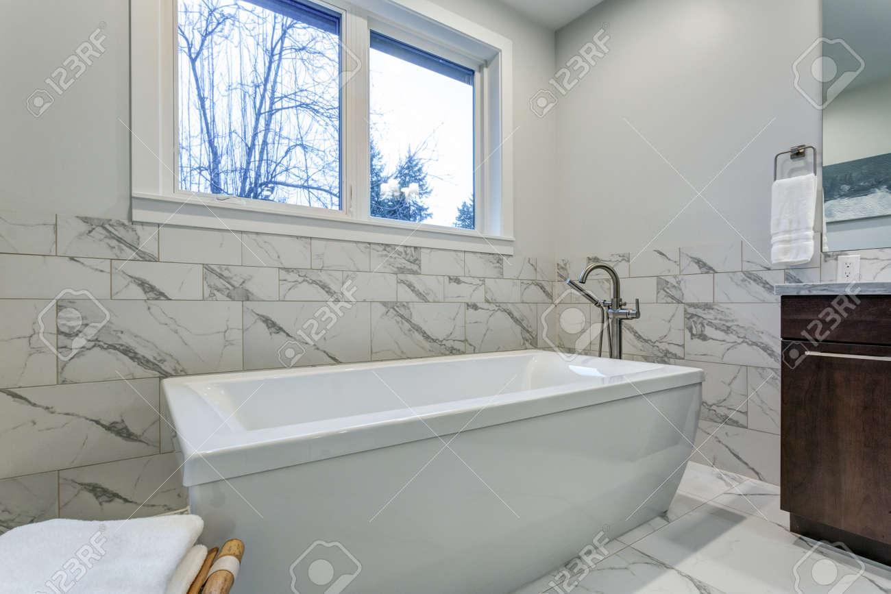 incredible master bathroom with carrara marble tile surround