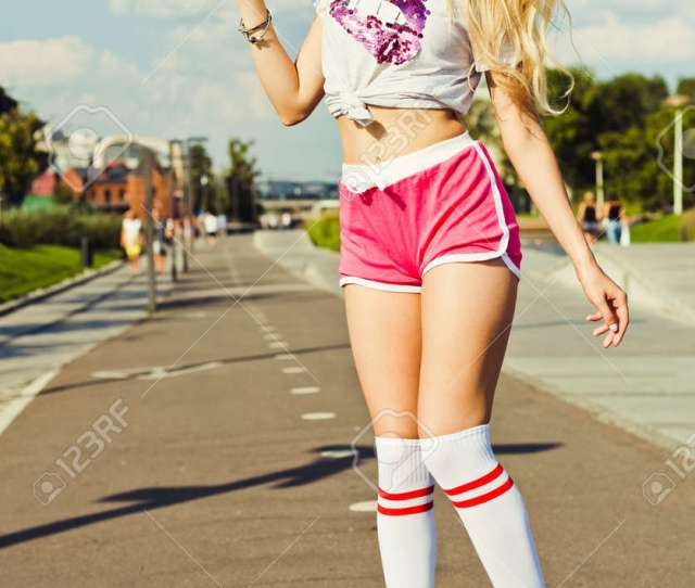 Beautiful Blonde Sexy Girl Posing On A Vintage Roller Skates In Pink Shorts And White T