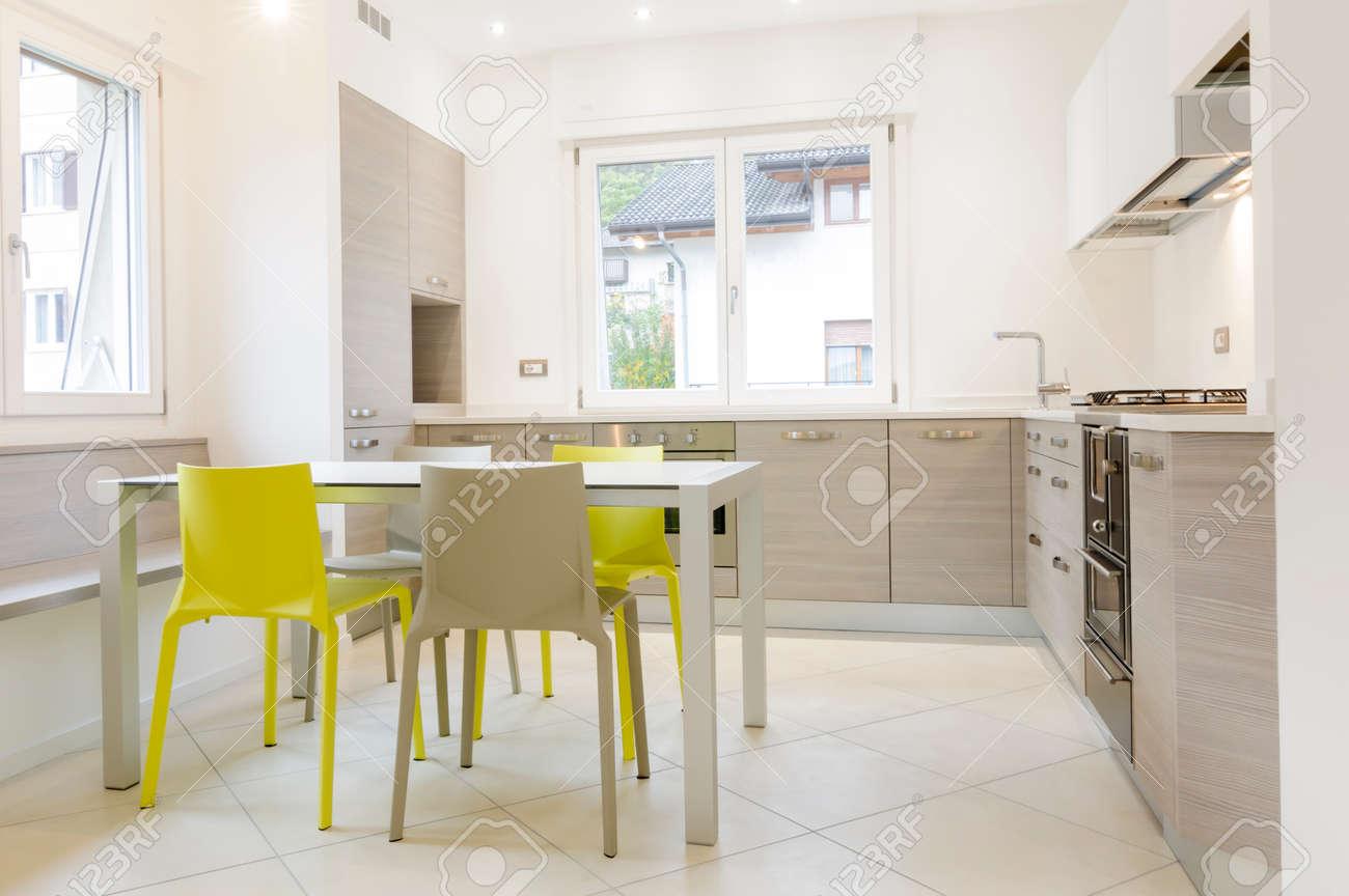 banque d images interieur de cuisine moderne avec armoires en bois table blanc gris et chaises jaunes