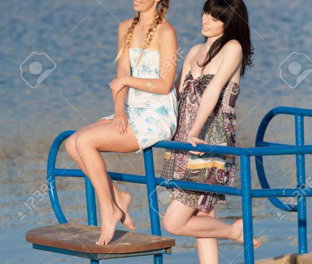 Stock Photo Young Women On Background Of Water Two Barefoot Girls In Sundresses On Pier