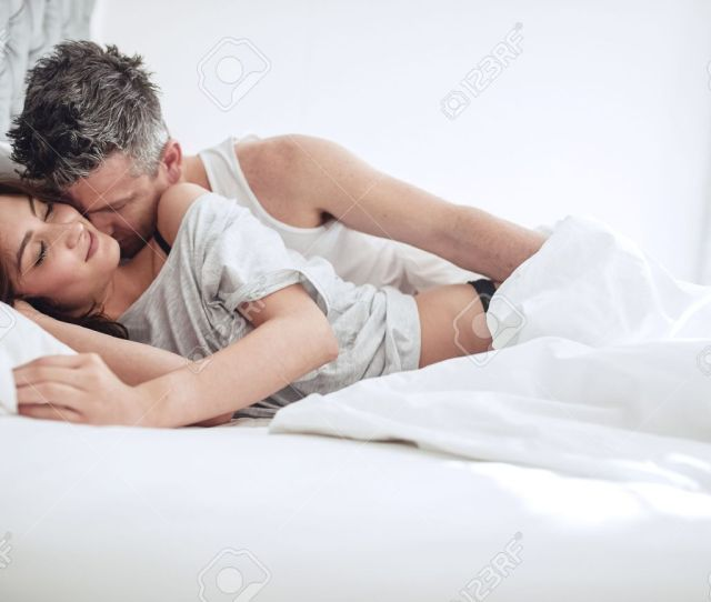 Intimate Young Couple Enjoying Sensual Foreplay On Bed Man Kissing On Neck Of Woman