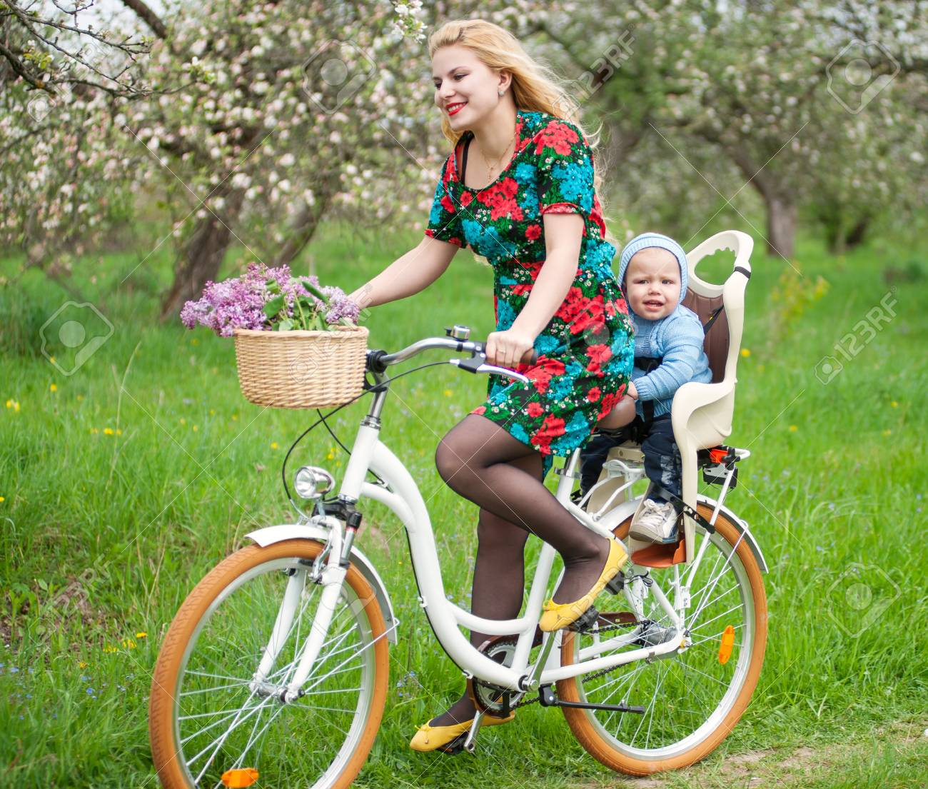the bike chair kartell mademoiselle blonde female with long hair in dress riding city bicycle baby