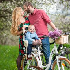 The Bike Chair Baby Doll With Potty Happy Sitting In Bicycle Against Kissing Parents On Background Of Blooming Trees