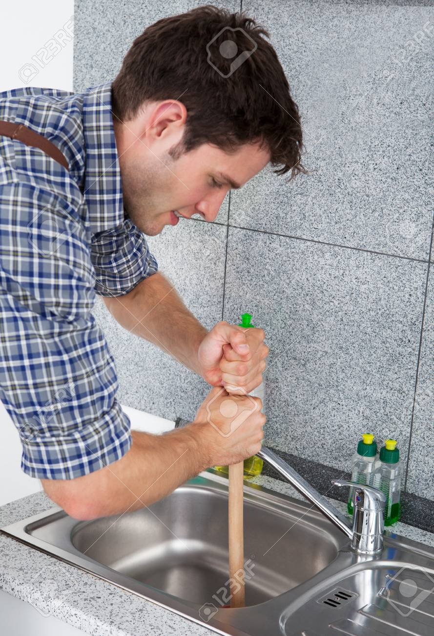 https www 123rf com photo 23361906 young handsome man using plunger in kitchen sink html