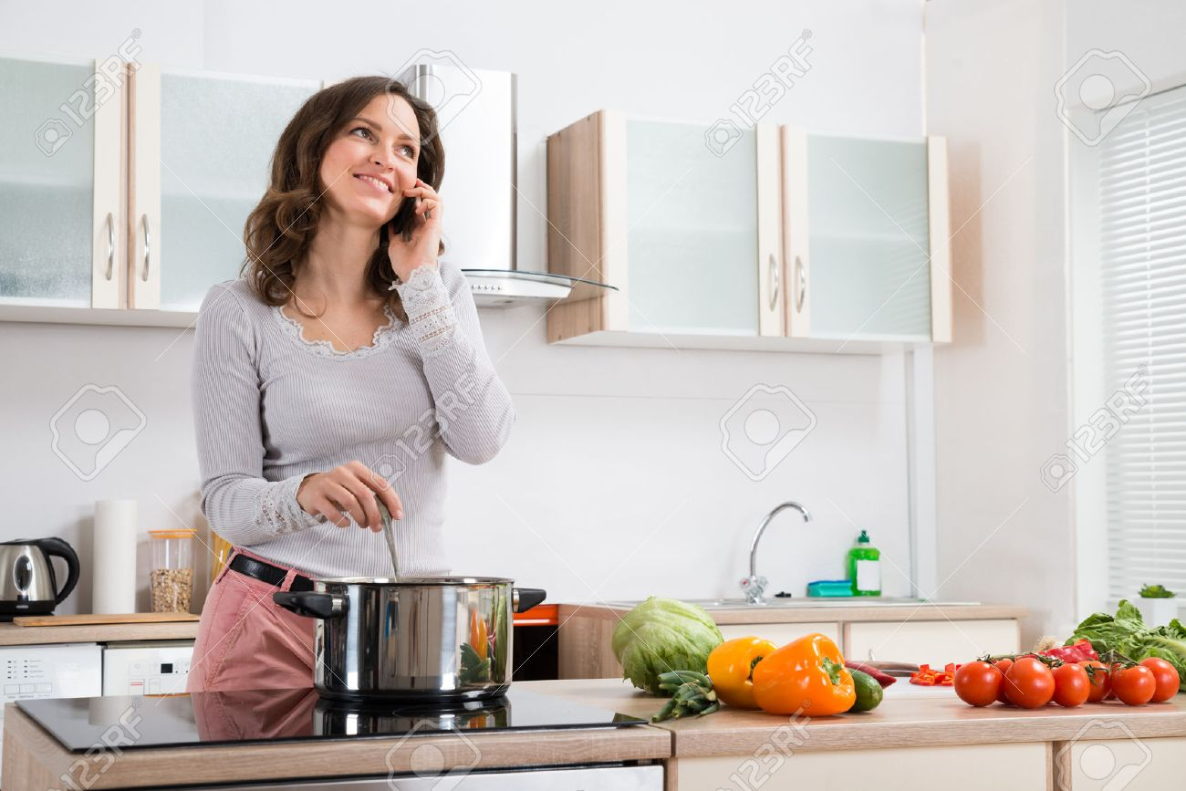 kitchen phone linoleum flooring happy woman talking on mobile while cooking in stock photo 43694325