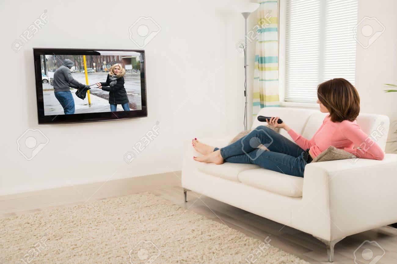 https fr 123rf com photo 53332542 jeune femme couch c3 a9e sur le canap c3 a9 tenant c3 a0 distance en regardant la t c3 a9l c3 a9vision html