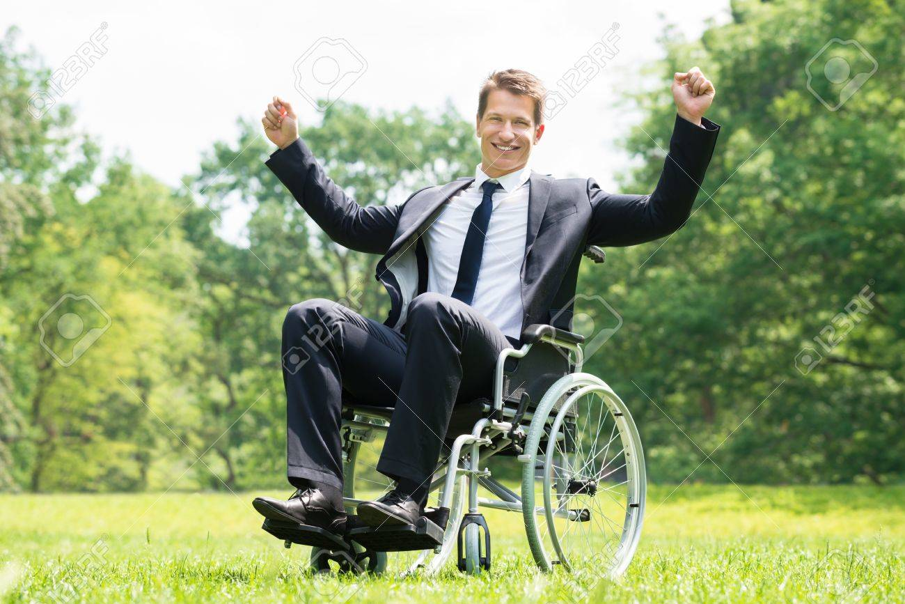 wheelchair man amish adirondack chairs happy young disabled on with raised arms in park stock photo 61417027