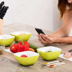 Kitchen Phone Task Lighting Close Up Of Woman Using Mobile At Countertop In Stock Photo 69329784