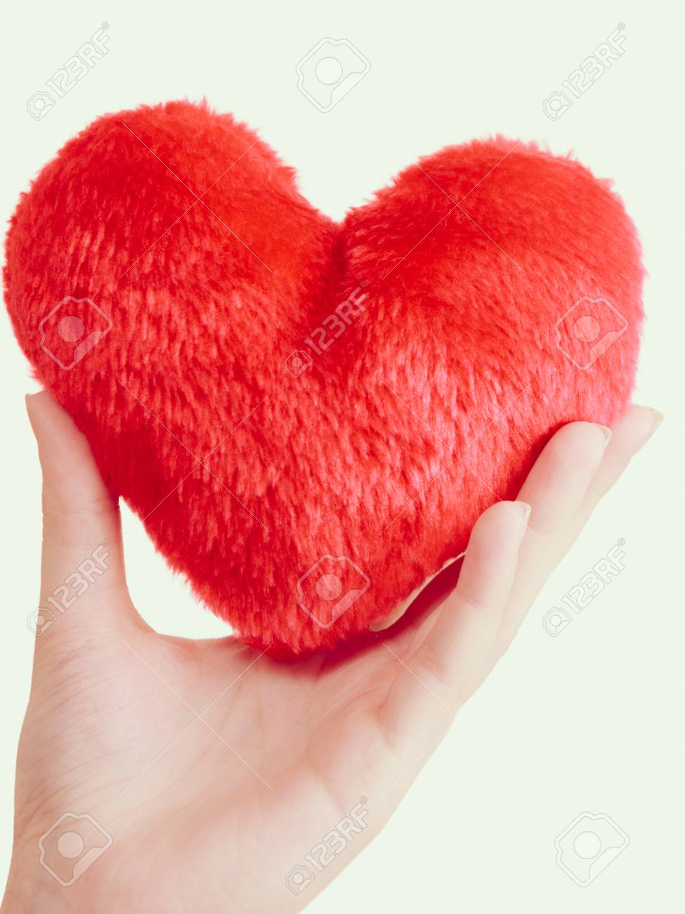 woman hand holding small romantic red heart shaped pillow perfect