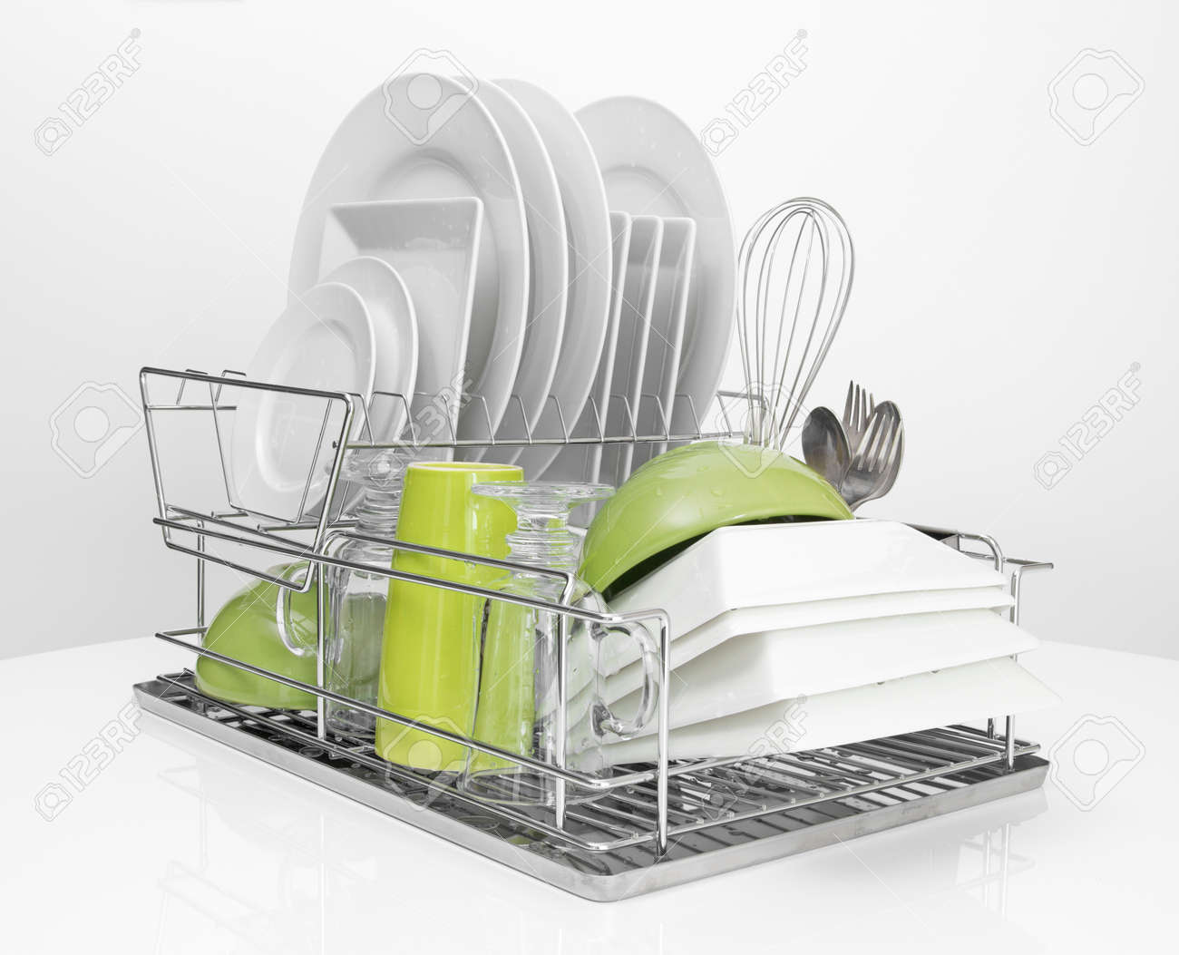 kitchen drying rack dish soap dispenser bright dishes on a metal white background stock photo 16674106