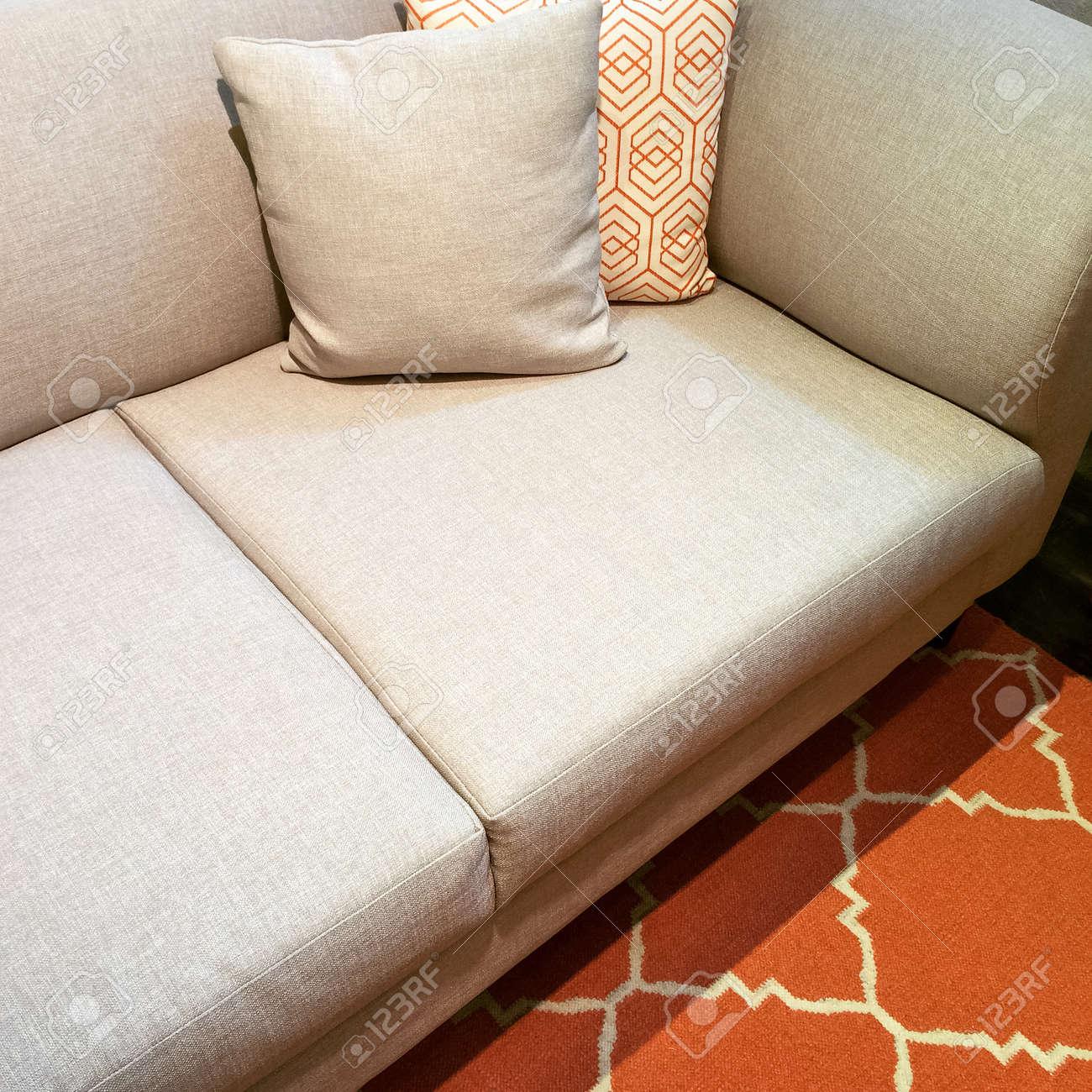 canape gris confortable avec des coussins sur le tapis orange