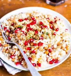 stock photo traditional east asian meal plate of warm salad with couscous chickpea pomegranate seeds lemon zest almond flakes and dill on a wooden  [ 866 x 1300 Pixel ]