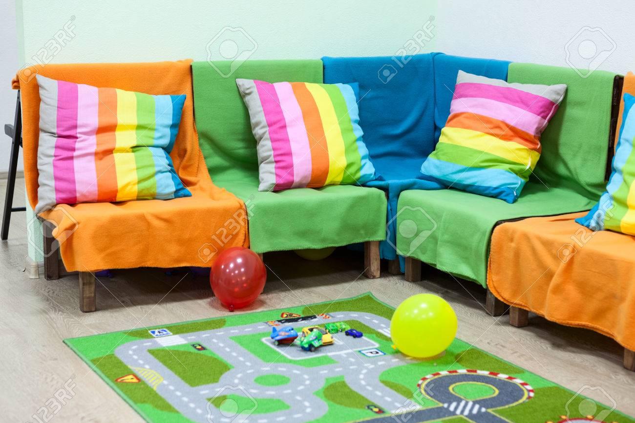 canape d angle avec coussins aux rayures colorees des ballons a l etage dans la chambre