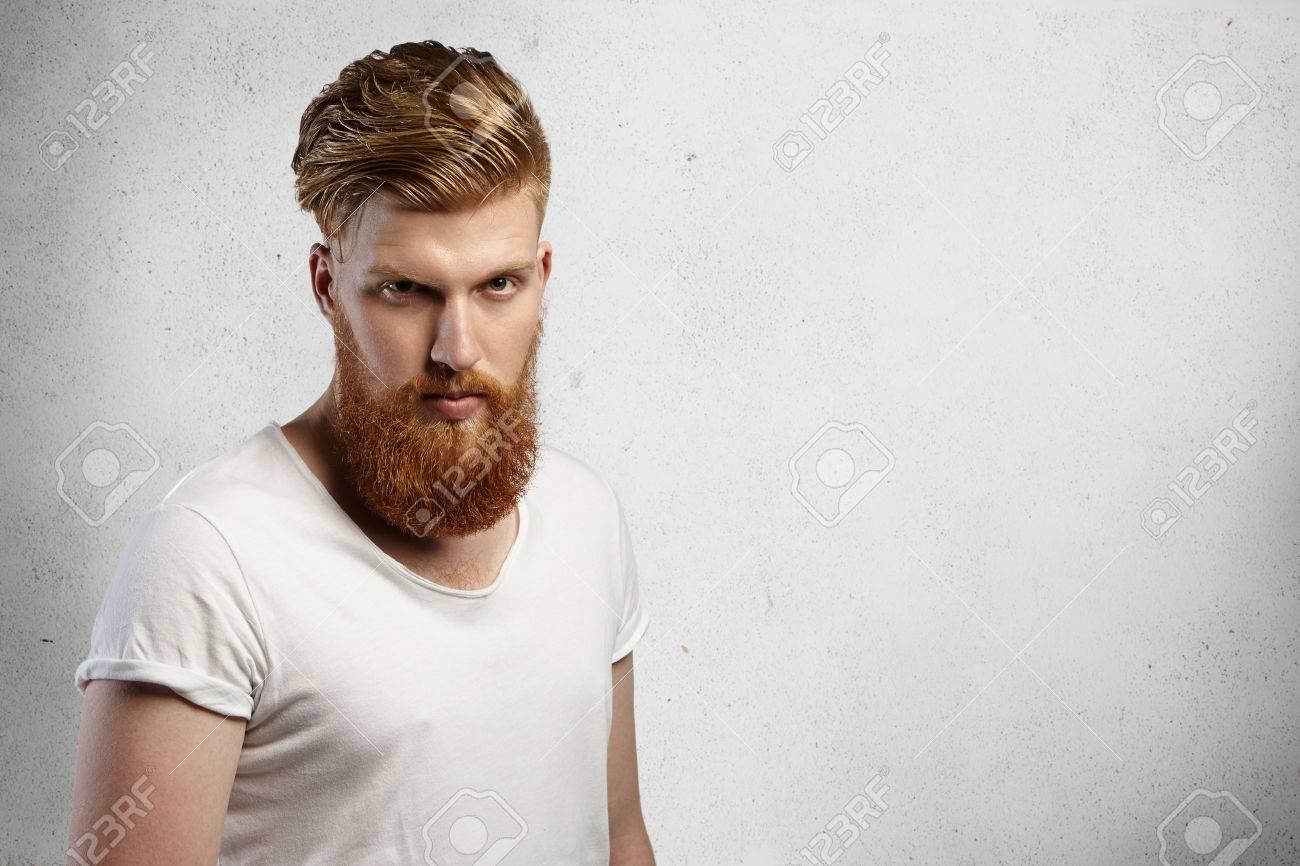 beau jeune homme hipster barbu coupe elegante regardant debout grave ou en colere en studio contre blanc fond mur avec copie espace pour votre contenu