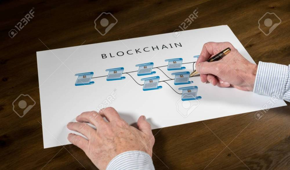 medium resolution of blockchain schematic on printout on desk with senior technology executive pointing at one of the encrypted