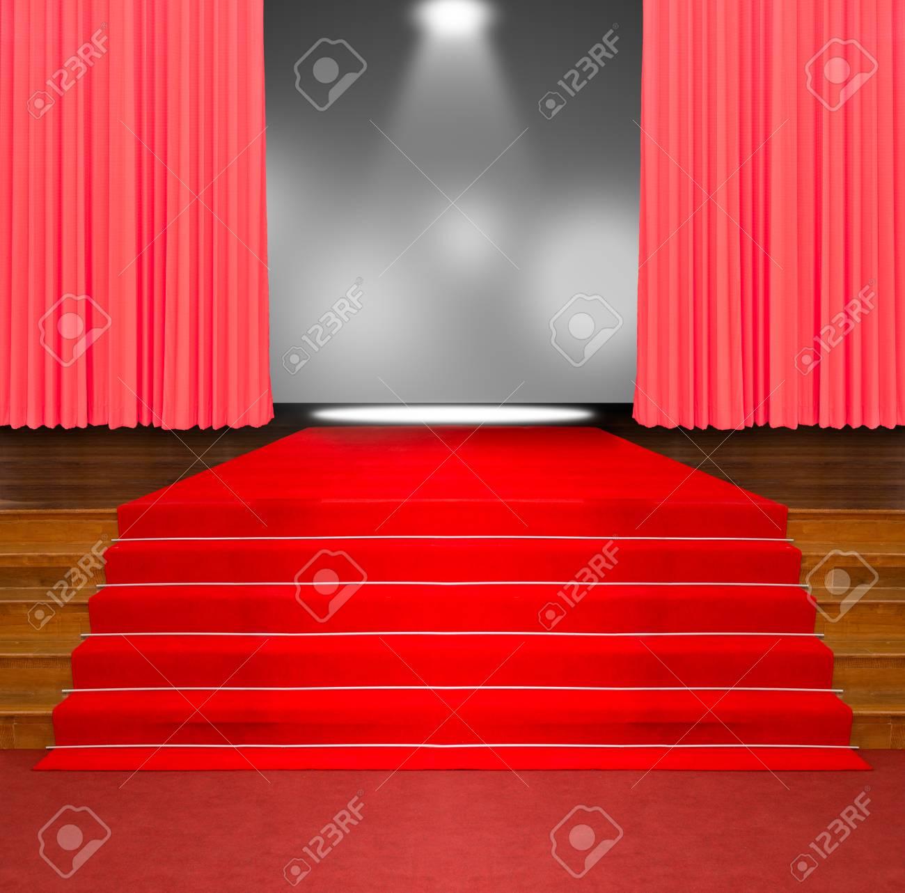 tapis rouge sur les escaliers en bois et rideau rouge avec fond de lumiere spot