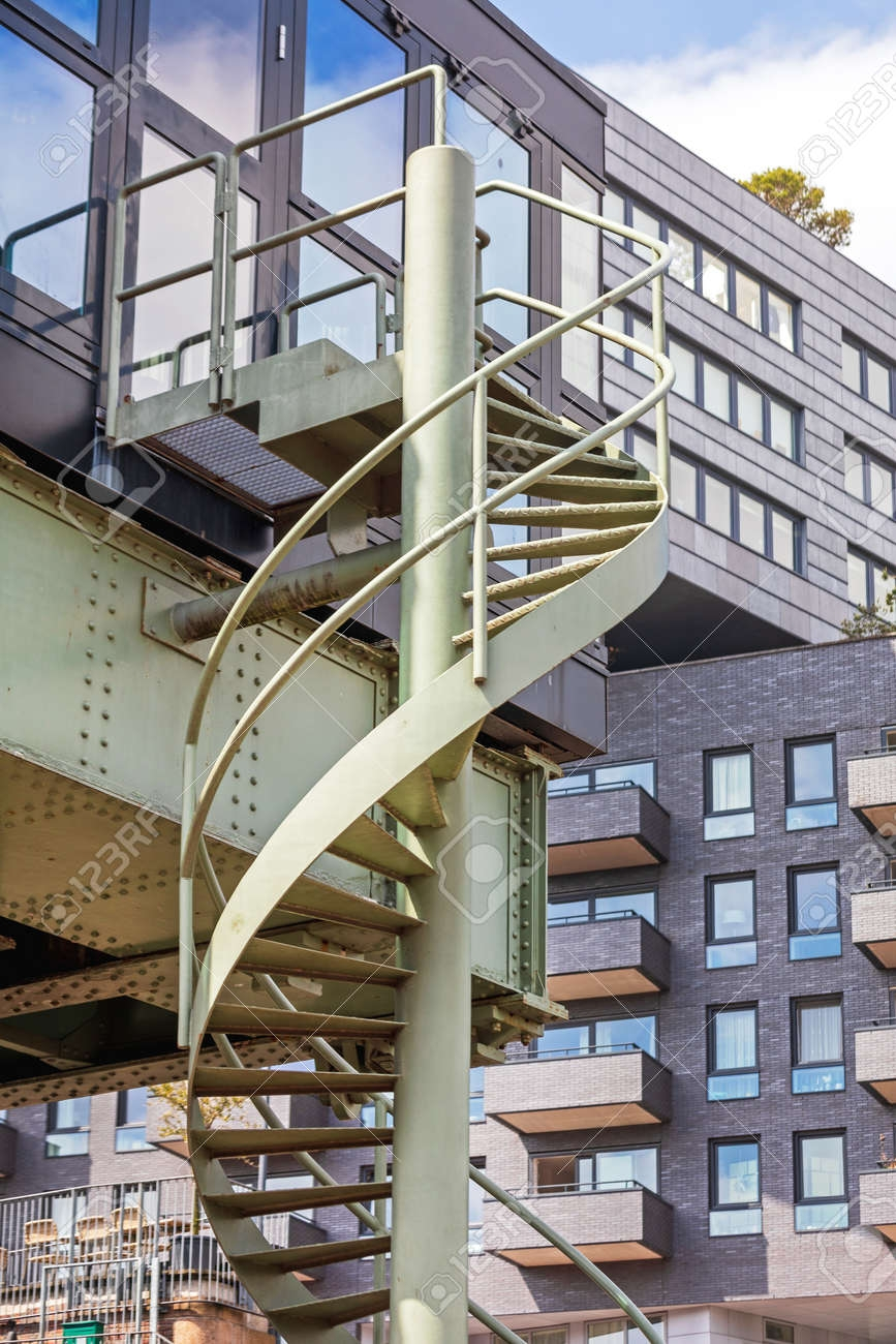 Metal Spiral Stairs Structure At Building Exterior Stock Photo | Exterior Metal Spiral Staircase | Rustic Metal | Deck | Crystal Handrail | Bar Modern | Railing