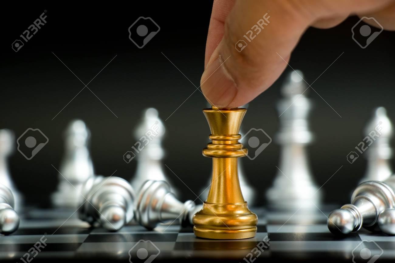 homme d affaires detiennent roi d or avec un pion d argent se coucher dans le jeu d echecs sur fond noir concept pour vitory dans les affaires le