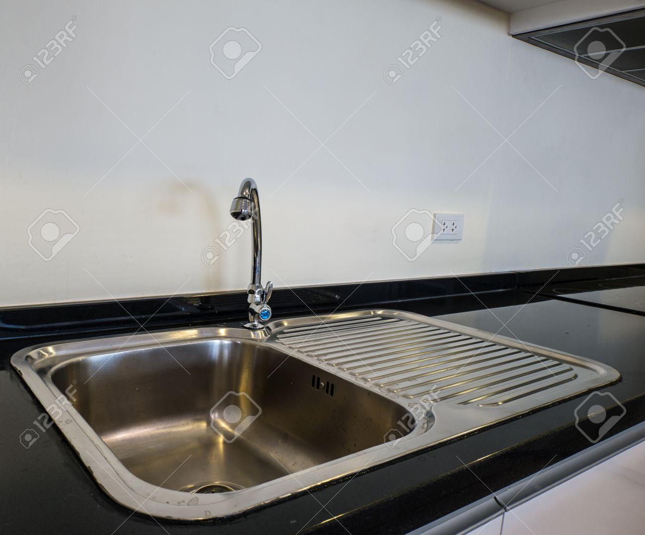 bowl stainless steel kitchen sink on a black granite worktop