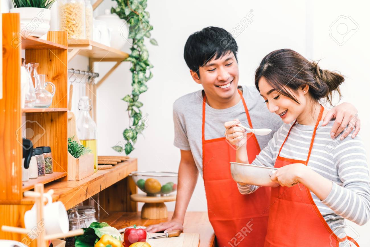 kitchen wear farm decor young asian lovely couple cooking together at home stock photo red apron making lunch meal girl taste soup using spoon