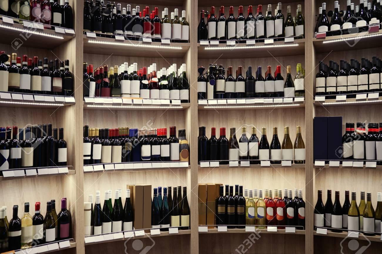 Wine Bottles On Wooden Shelves At Liquor Store