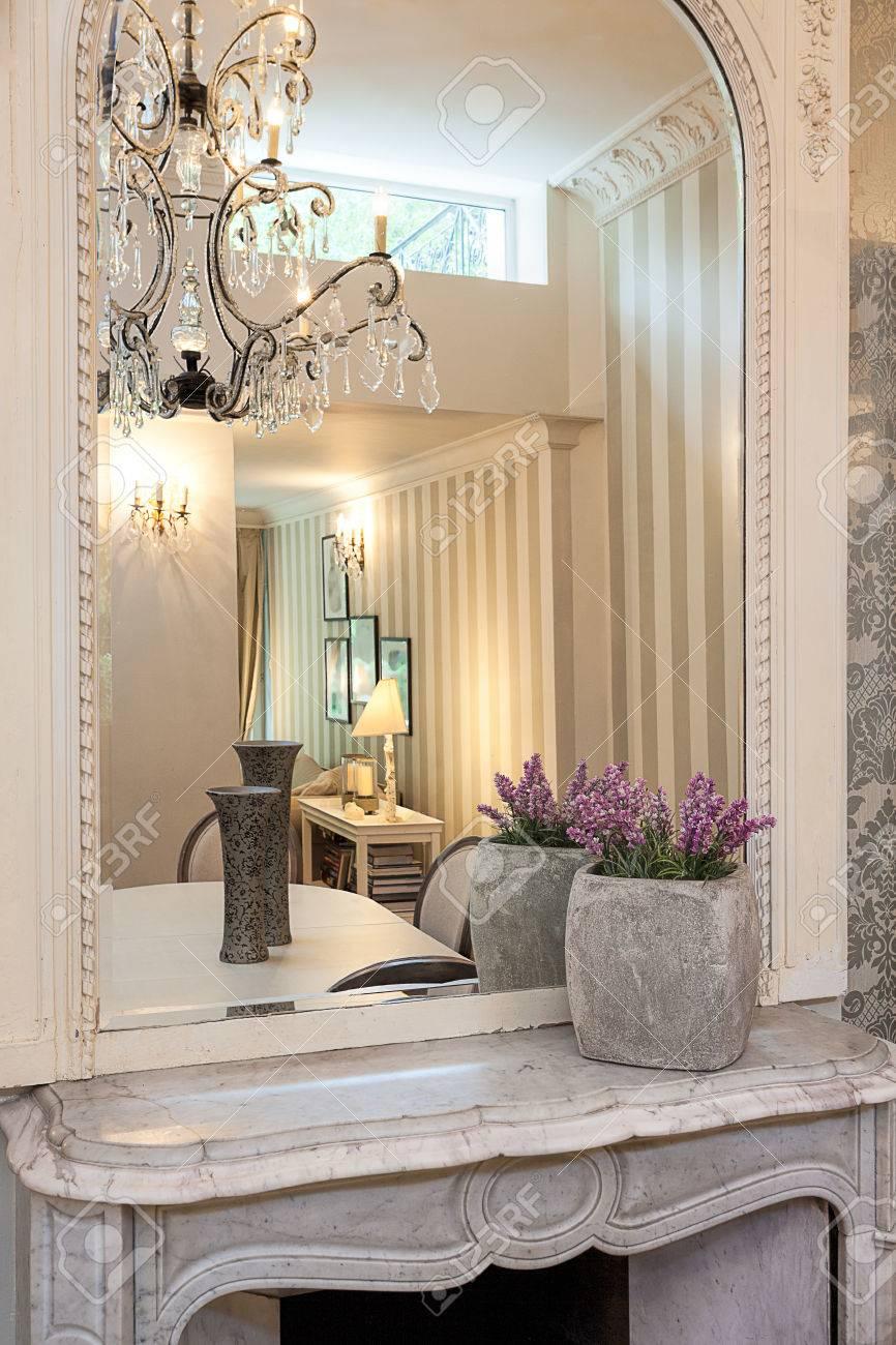 manoir de cru une cheminee en pierre blanche avec des fleurs et un miroir au dessus