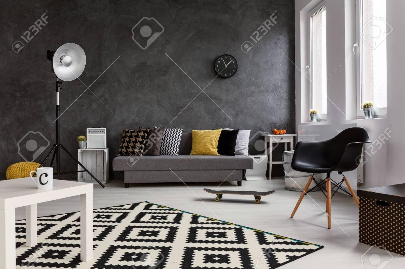 salon gris avec canape chaise lampe debout petite table blanc et noir et blanc motif tapis