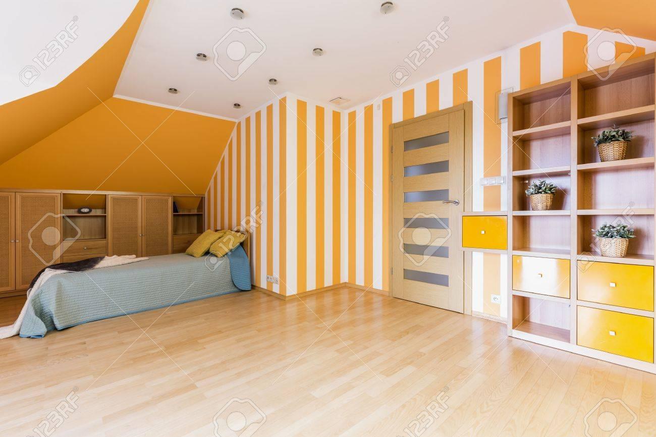 chambre moderne et spacieuse en orange et blanc avec un lit simple des panneaux de plancher et une etagere murale