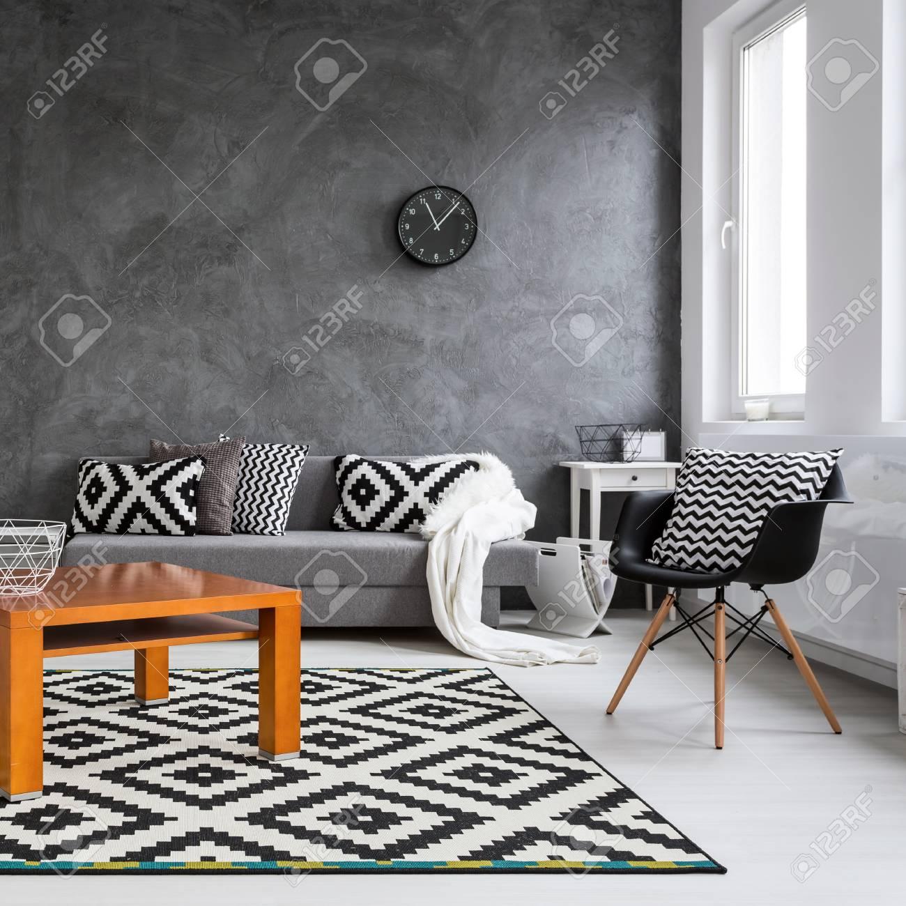 gris salon avec canape chaises lampe debout petite table en bois et decoration en noir et blanc