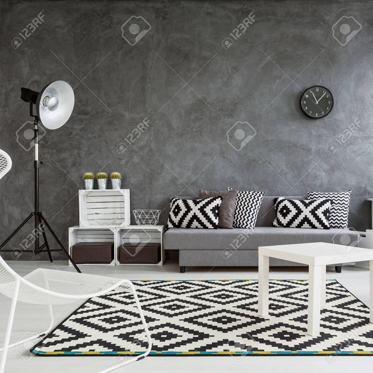 grand salon decore avec style murs gris blanc plancher en bois et decorations blanches et noires