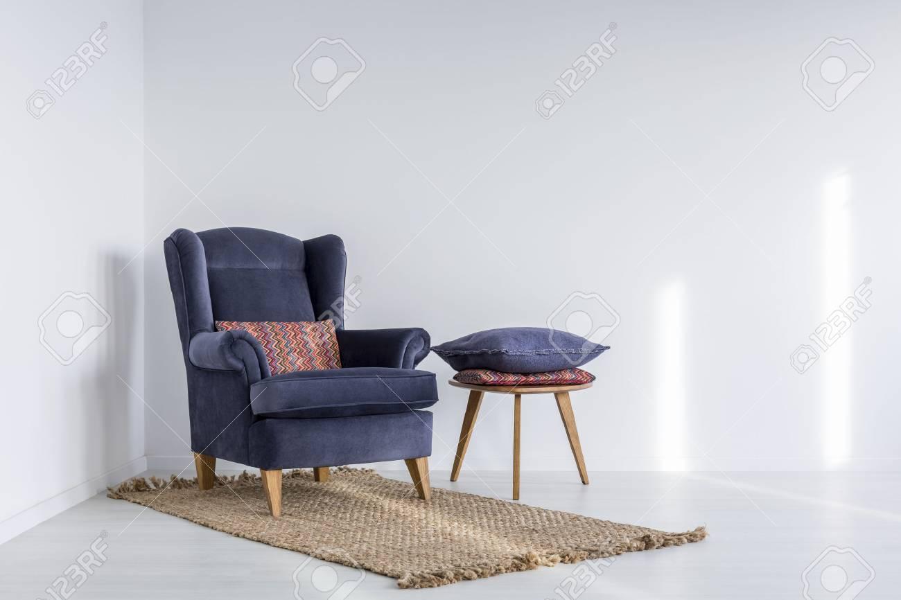 interieur blanc avec un fauteuil bleu marine tapis et table d appoint