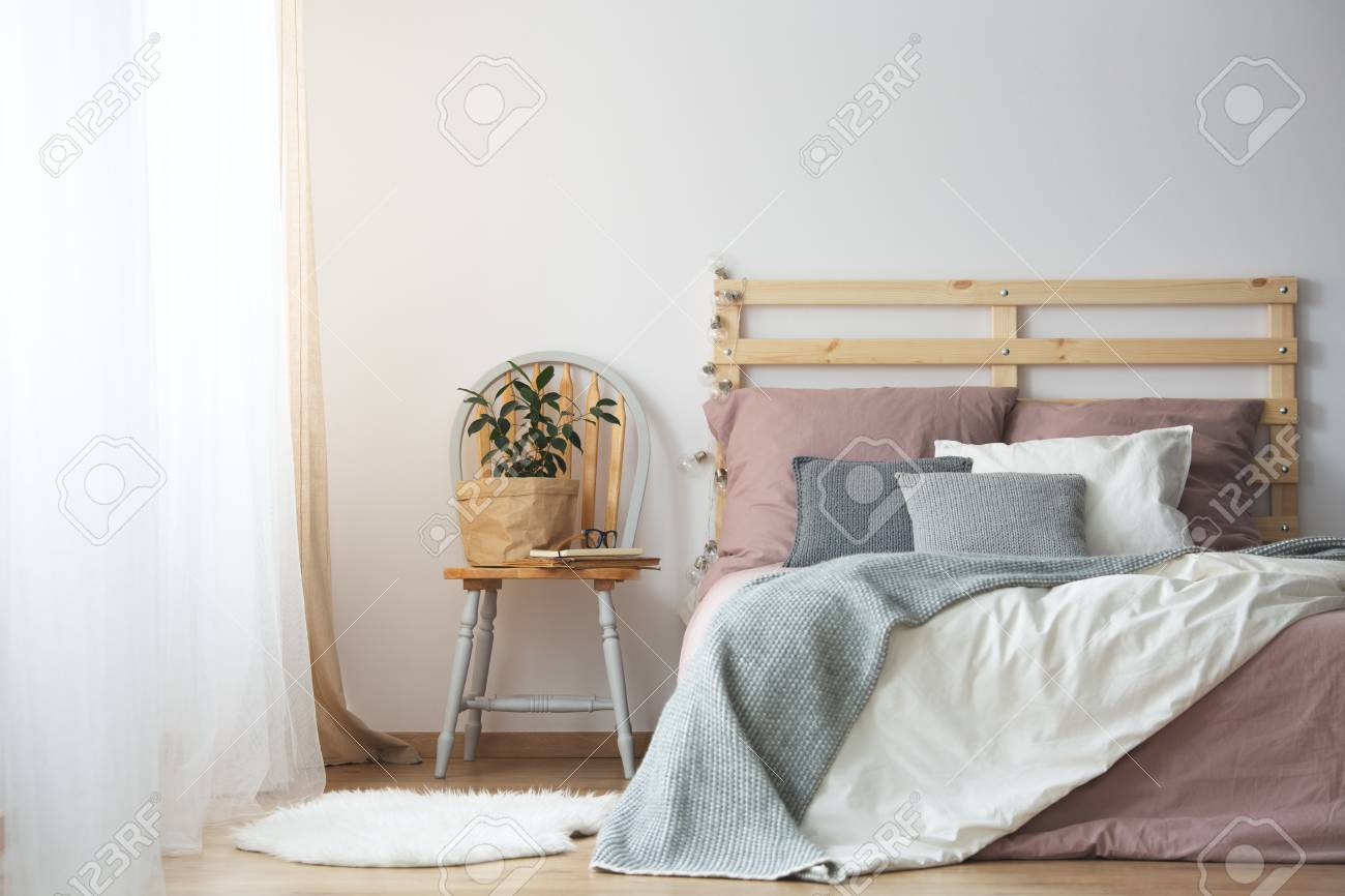 Wooden Bed With Bedding In Cozy Grey And Pink Bedroom