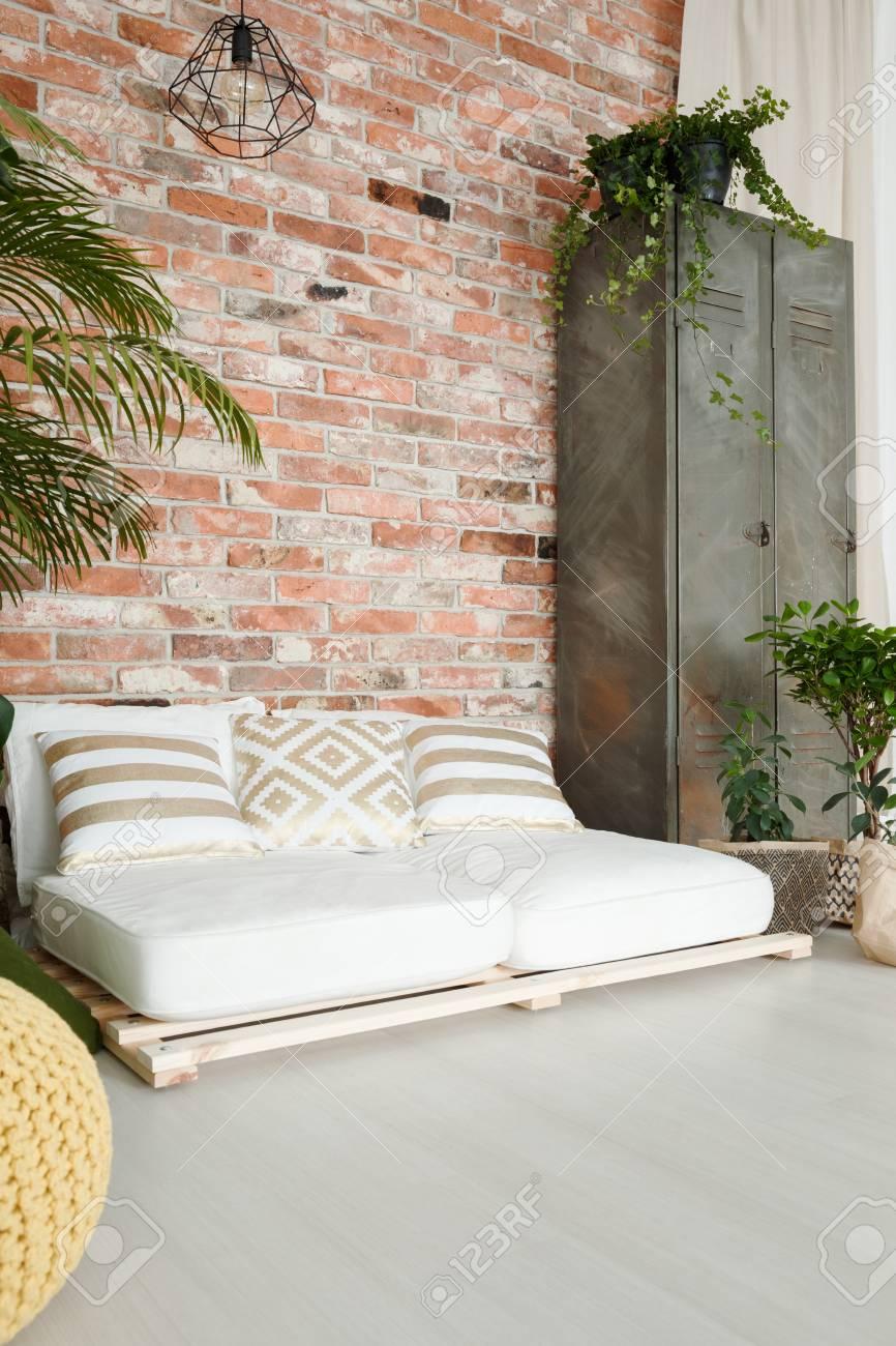 canape blanc confortable par le mur de brique rouge dans une chambre spacieuse banque d images et photos libres de droits image 81873655